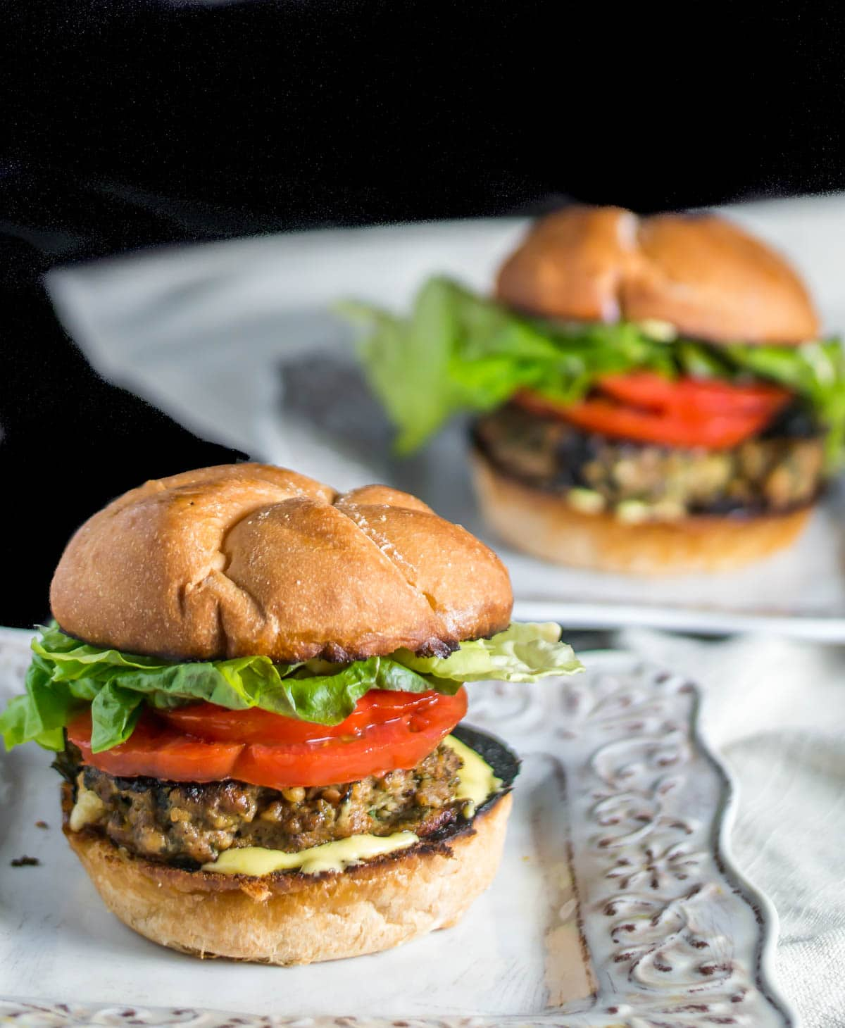 2 square plates with healthy Mexican turkey burgers, linen napkins, and a black background.