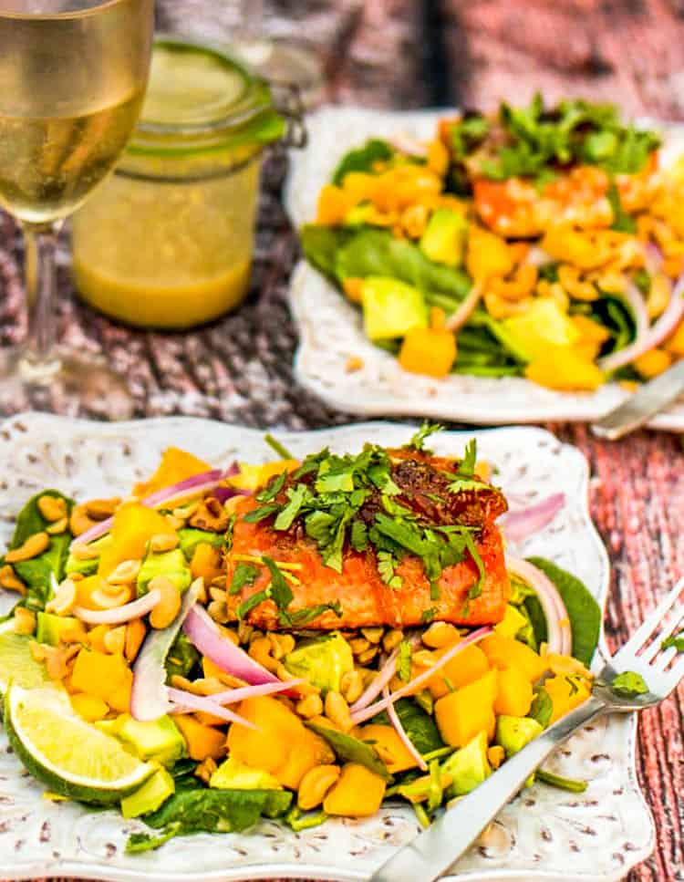 Seared salmon and spinach salad with mango, avocado, and cashews on 2 square  plates.