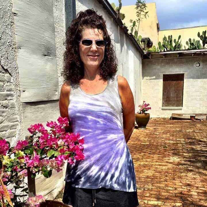 Tamara standing at the Roma Bluffs World Birding Center with bright flowers.