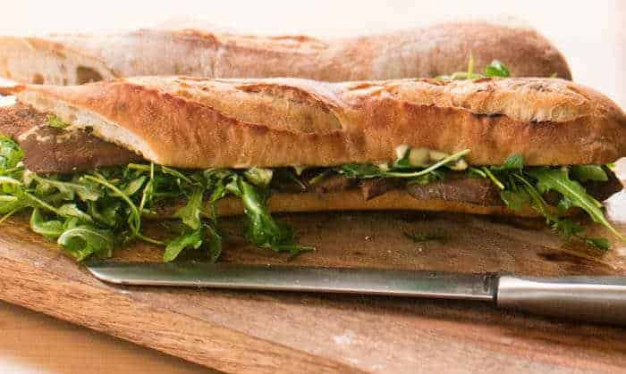 One long sandwich with sliced tongue, aioli, and lemony arugula salad on a cutting board before being cut into fourths.