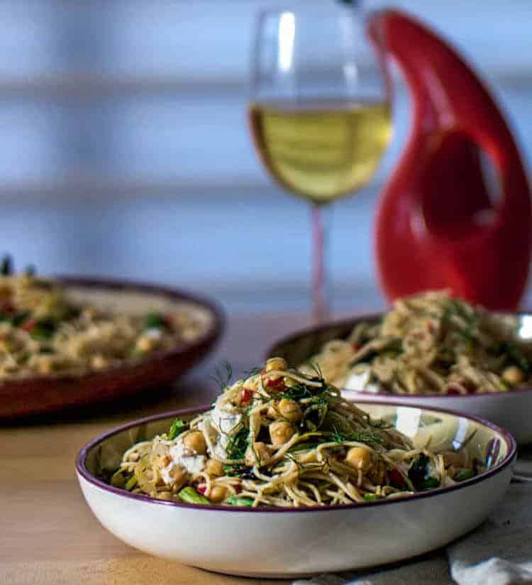 Lemony Pasta with Grilled Asparagus Hero Image - vegetarian pasta dish in a shallow ceramic bowl with a glass of white wine and olive oil cruet.