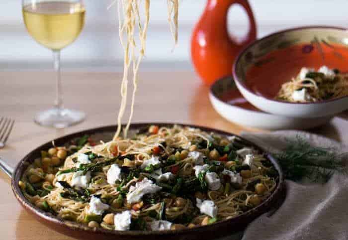 Lemony Pasta With Grilled Asparagus and Chevre in a shallow platter with a glass of white wine.
