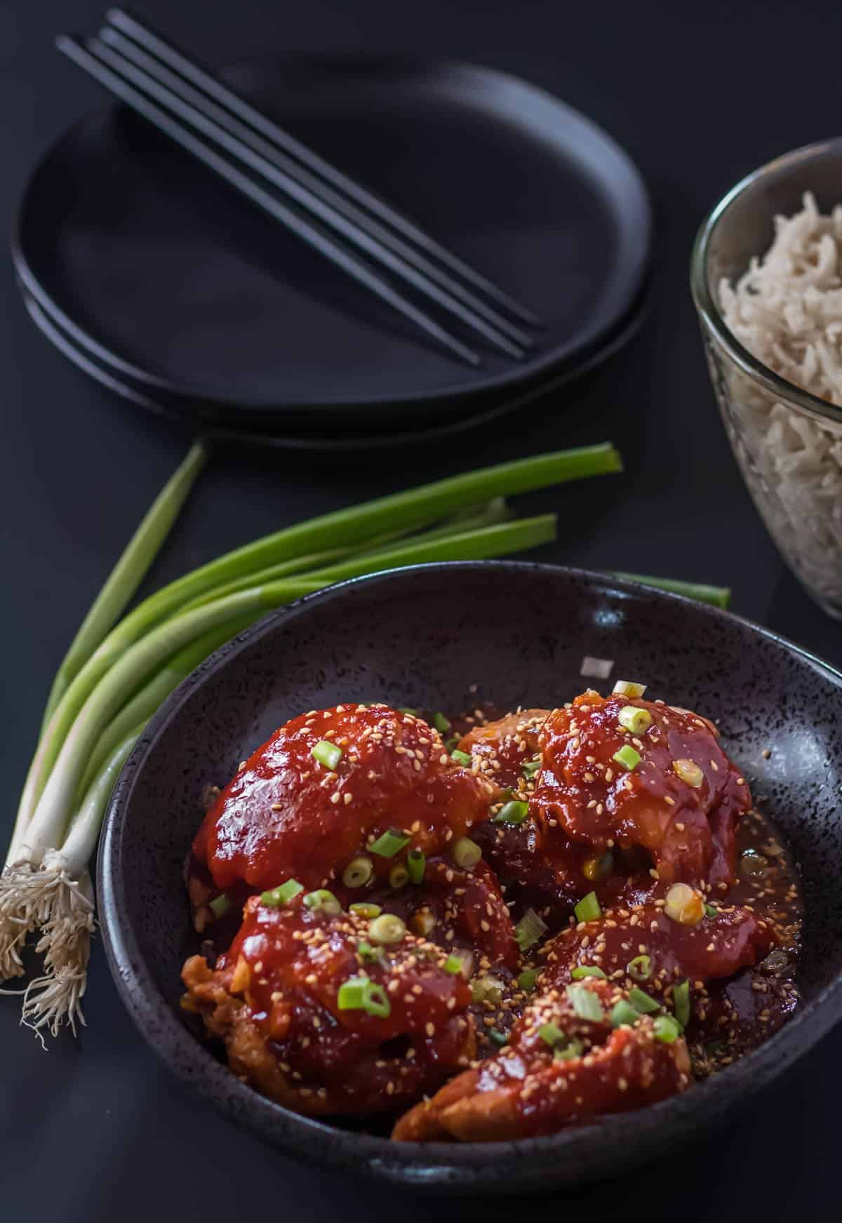 Instant Pot Korean Chicken Thighs in a black serving bowl alongside a bowl of jasmine rice with a bunch of scallions.