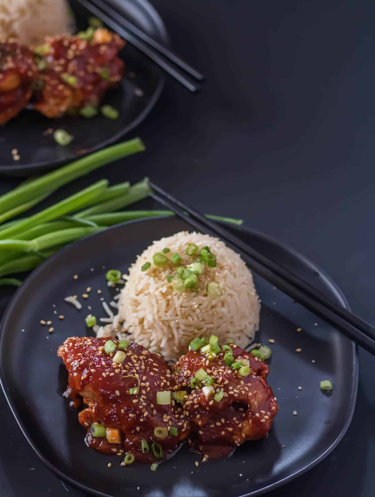 Instant Pot Korean Chicken Thighs on a round black plate with a scoop of rice, garnished with scallions and sesame seeds.