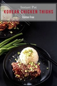 Instant Pot Korean Chicken Thighs on a round black plate with a scoop of rice and garnished with scallions and sesame seeds.