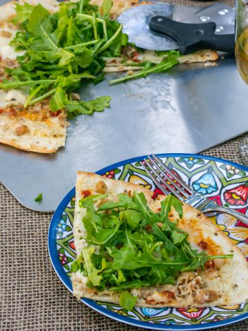 A slice of Clam and Chorizo Pizza on a blue plate with a fork and glass of white wine.