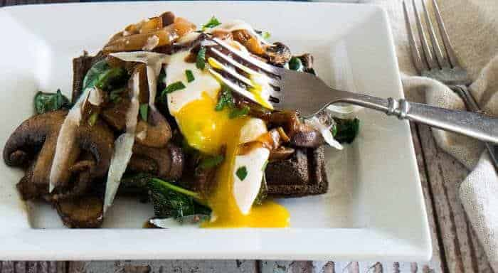 A savory buckwheat waffle with sautéed spinach, mushrooms, runny egg on a square white plate.