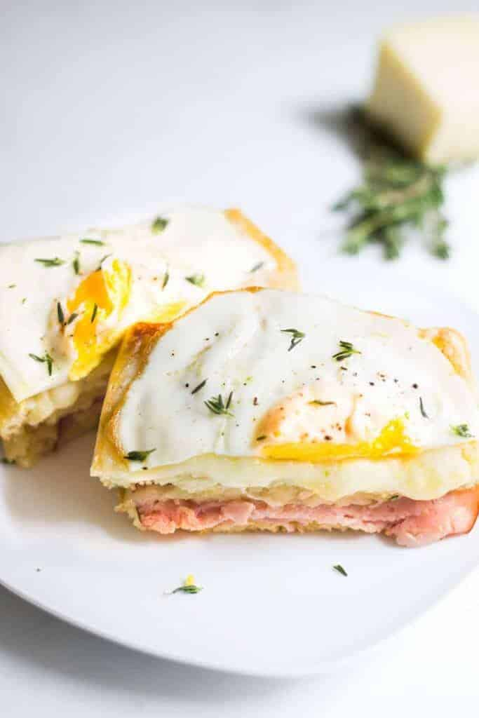 A savory waffle sandwiche with ham, cheese, and a soft fried egg sprinkled with fresh thyme.