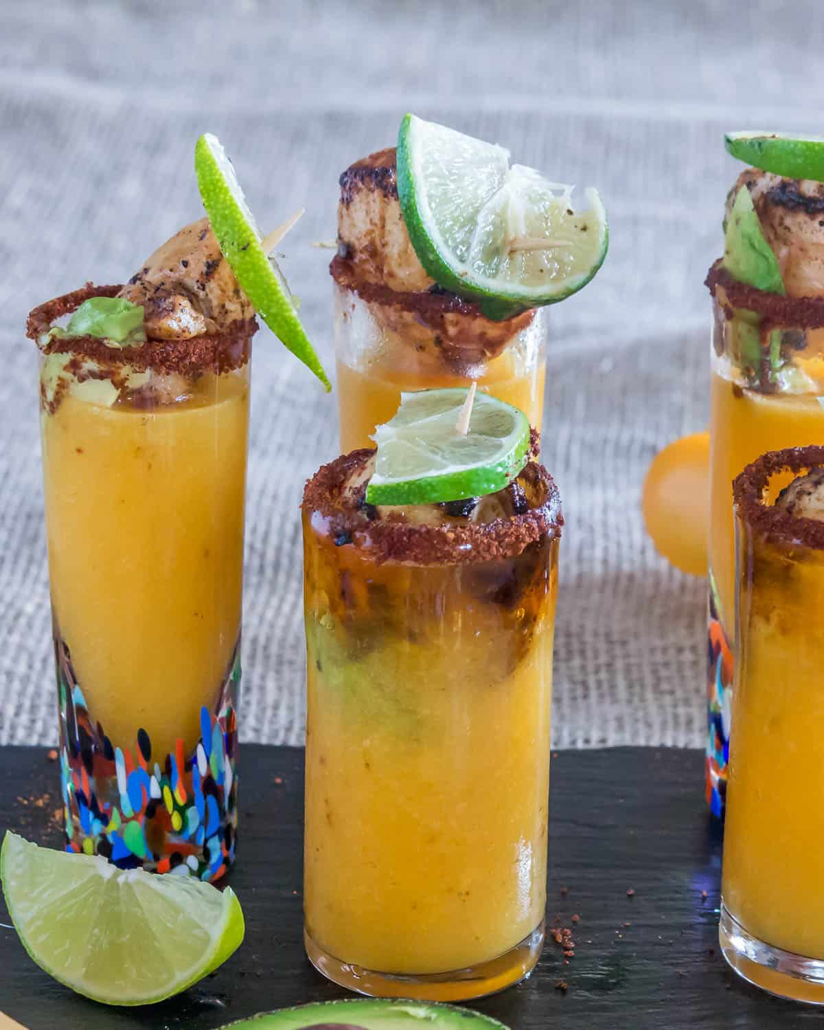 6 Spicy Scallop Shooters on a slate tray garnished with lime wedges.