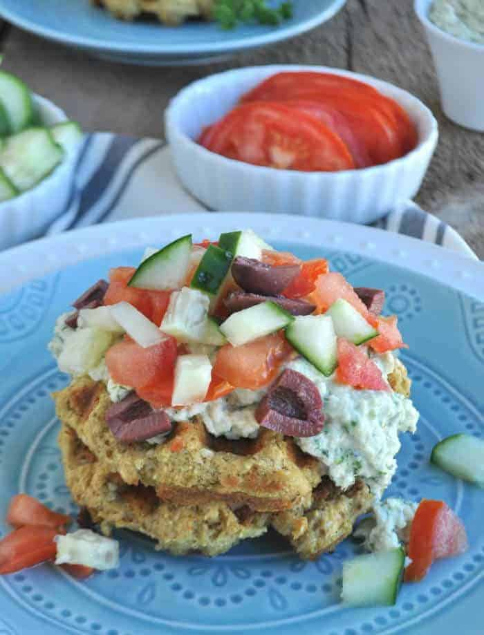 A savory falafel waffle with healthy artichoke tzatziki, cucumber, olive, tomato on a light blue plate.