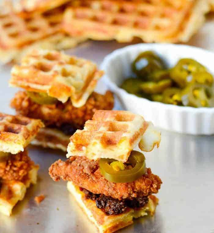 Savory cheddar waffle sliders with fried chicken and bacon jam with a bowl of jalapeno pickles.