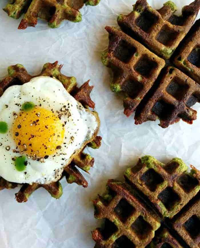 Savory multigrain and spinach waffles with a soft fried egg on parchment paper.