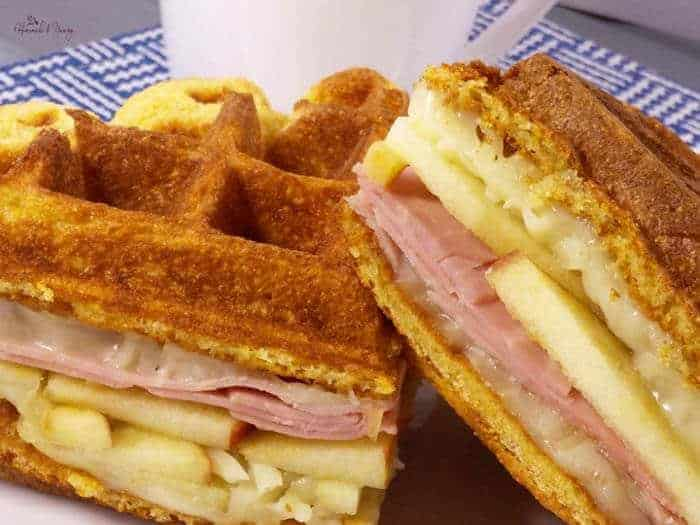 A savory waffle sandwich with ham, cheese, and apple slices on a blue and white checked placemat.