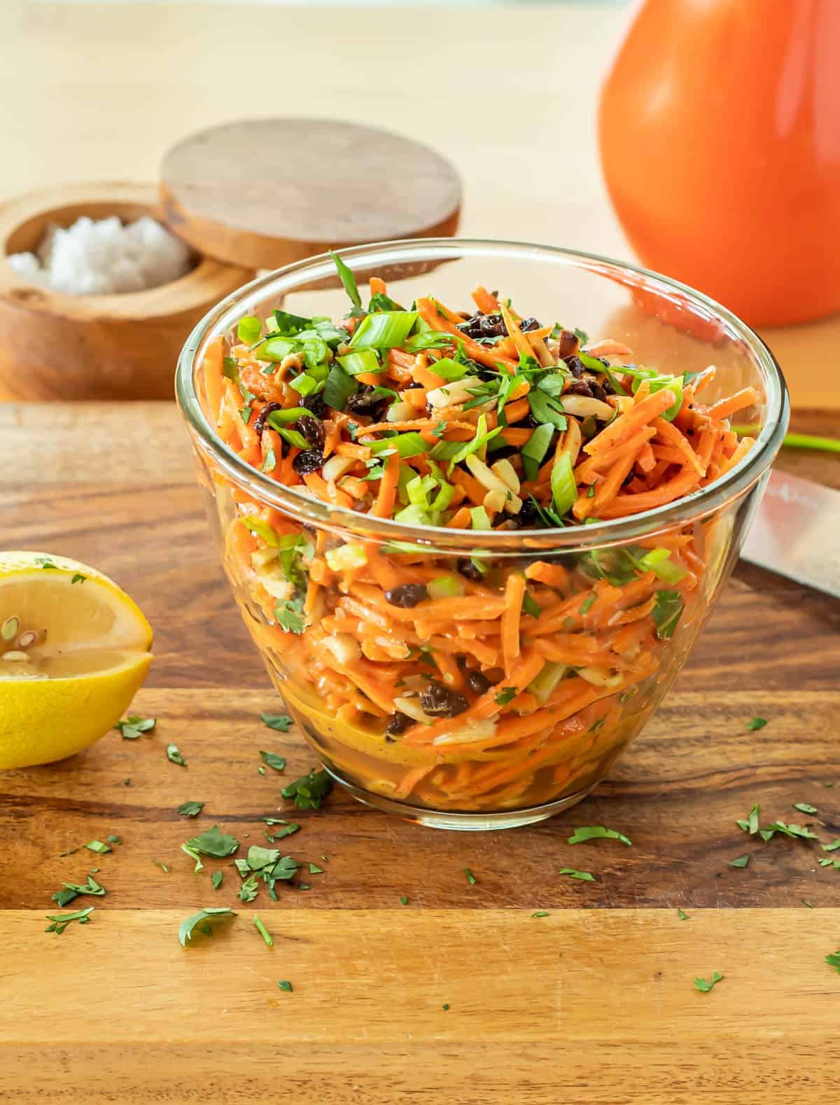 A clear glass bowl of Moroccan Carrot Salad with Lemon Dressing, a wood salt box and bottle of olive oil...