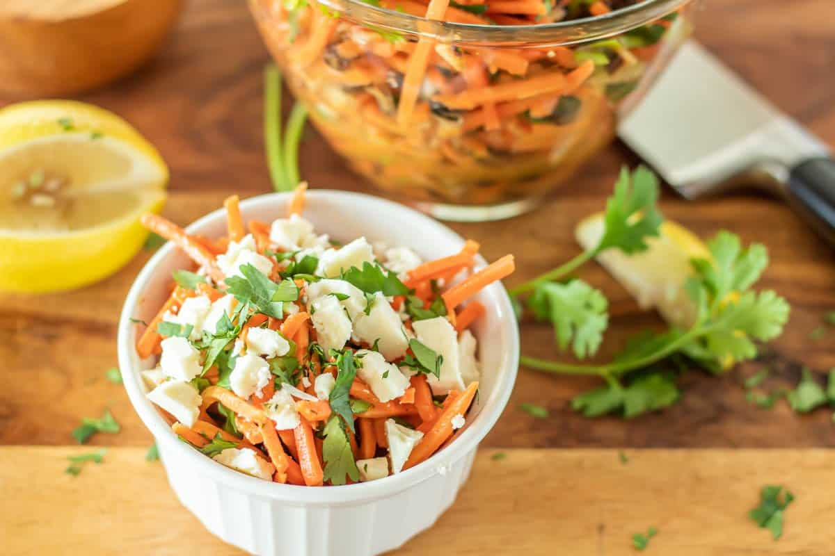 A white bowl of prepared Moroccan carrot salad with feta cheese and cilantro alongside lemon wedges on a wood cutting board.
