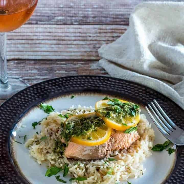 Instant Salmon and Rice with a lemon caper chimichurri on top on a bronze plate with a glass of wine.