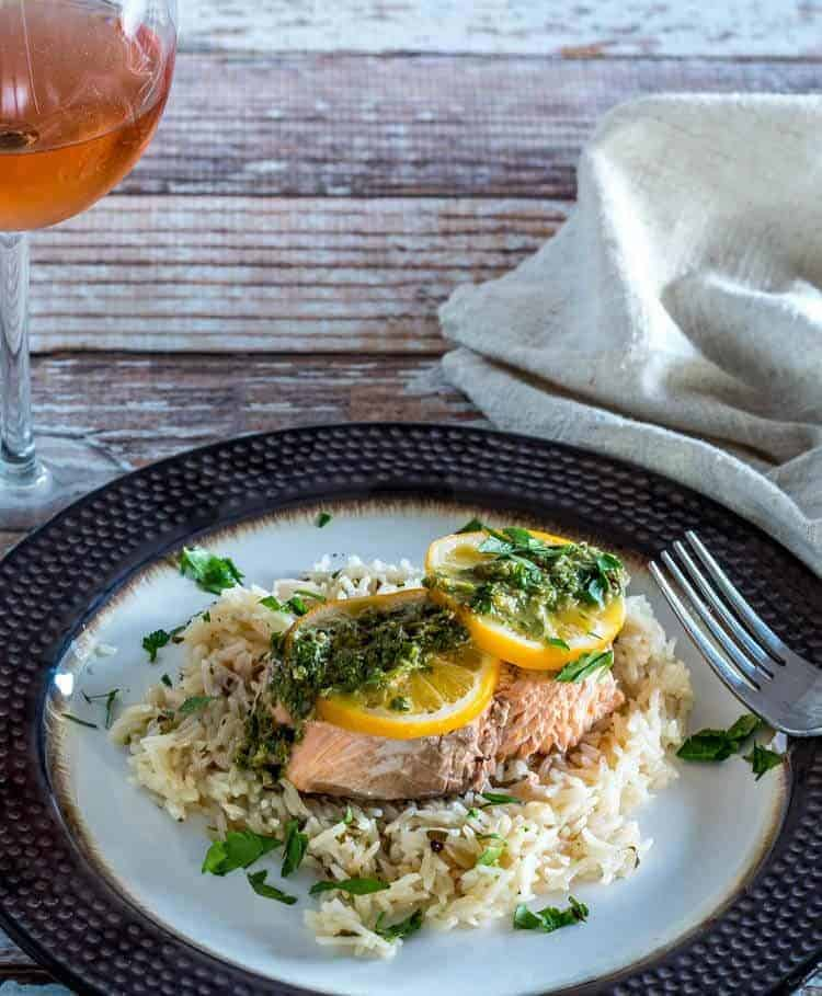 Instant Pot Salmon and Rice  with lemon caper chimichurri and Meyer lemon slices on a bronze plate with a glass of rosé.