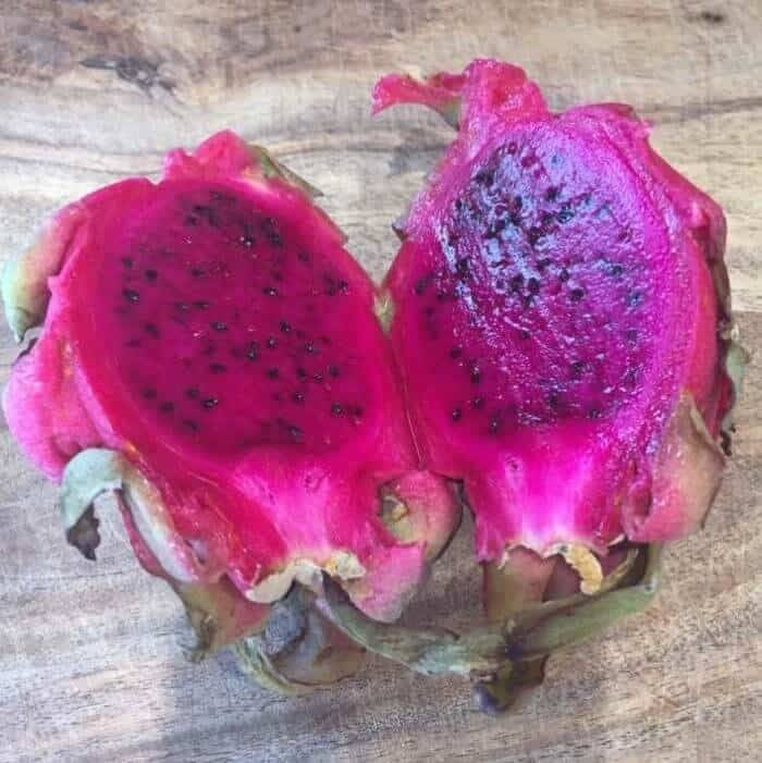 A pitaya/dragonfruit cut in half lengthwise.