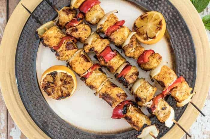 Ras El Hanout Chicken Kebabs close up on a bronze ceramic plate with a yellow charger.