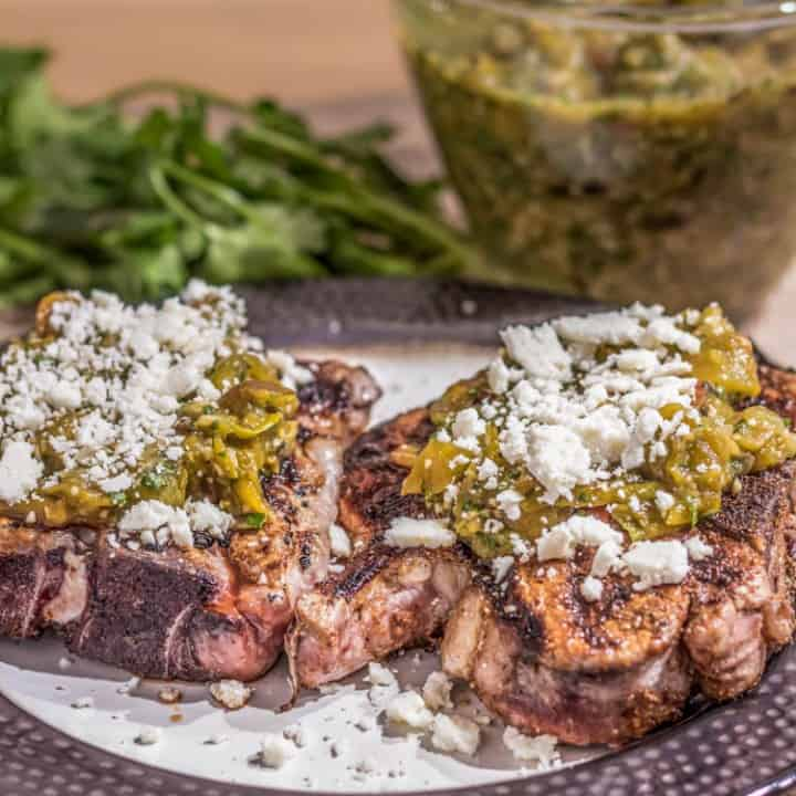 A bronze rimmed plate with 2 Mexican pork chops topped with salsa verde and cotija.