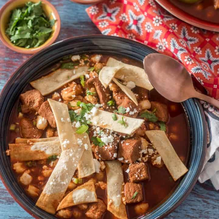 A close up of Instant Pot Red Chile Posole in an off-white bowl with silver spoon, cilantro garnish, lime wedge.