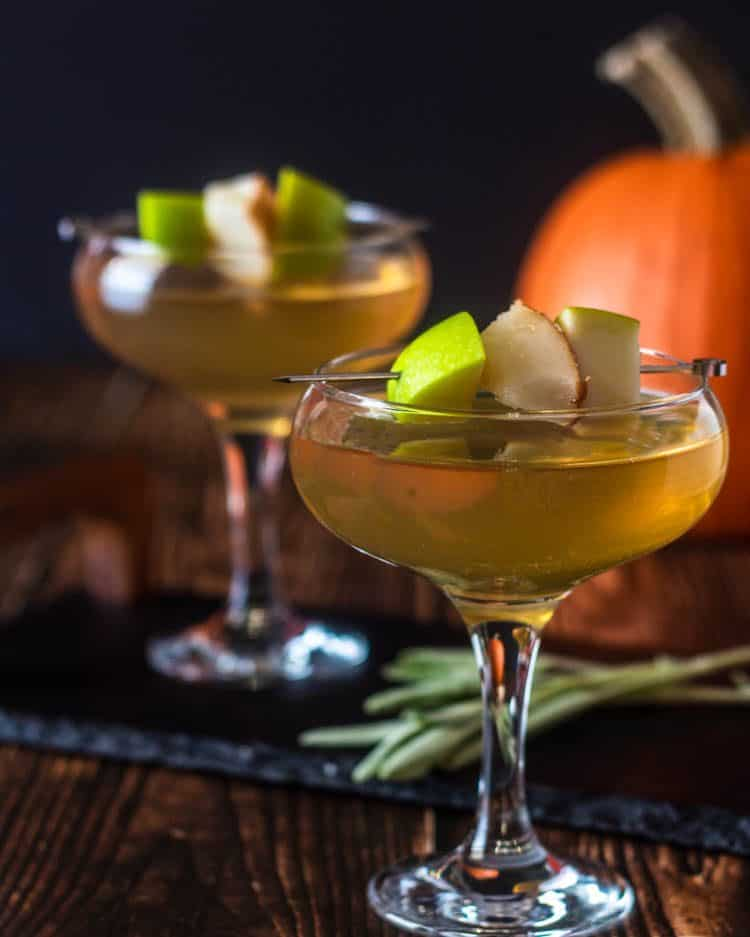 1 Apple and Pear Martini close up, 1 in the background on a slate tray, garnished with fresh apple and pear with a pumpkin in the background and fresh sage in the foreground.