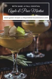 2 coupe glasses with Apple and Pear Martini on a wood background beside a small pumpkin.