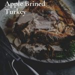 My Herb and Apple Brined turkey November 2019 on a white ceramic platter on a grey background with carving tools.