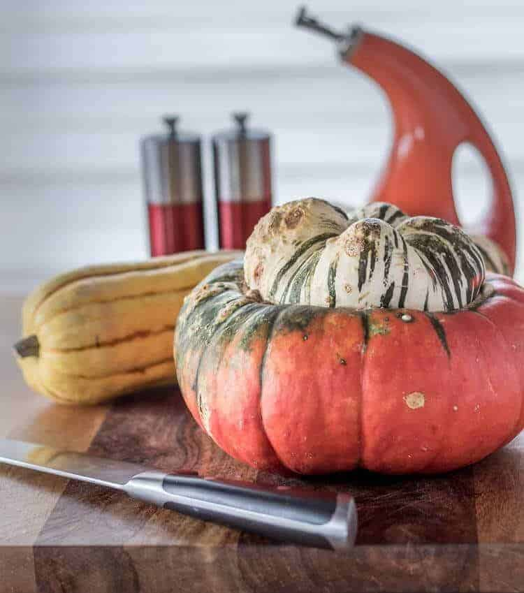 A whole, uncut turban squash and a delicata squash on a cutting board with a knife.