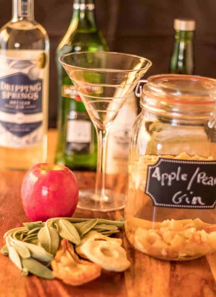 Apple, Pear, and Sage Martini ingredients alongside a vacuum-sealed jar of apple and pear infused gin ready to make this unique cocktail.
