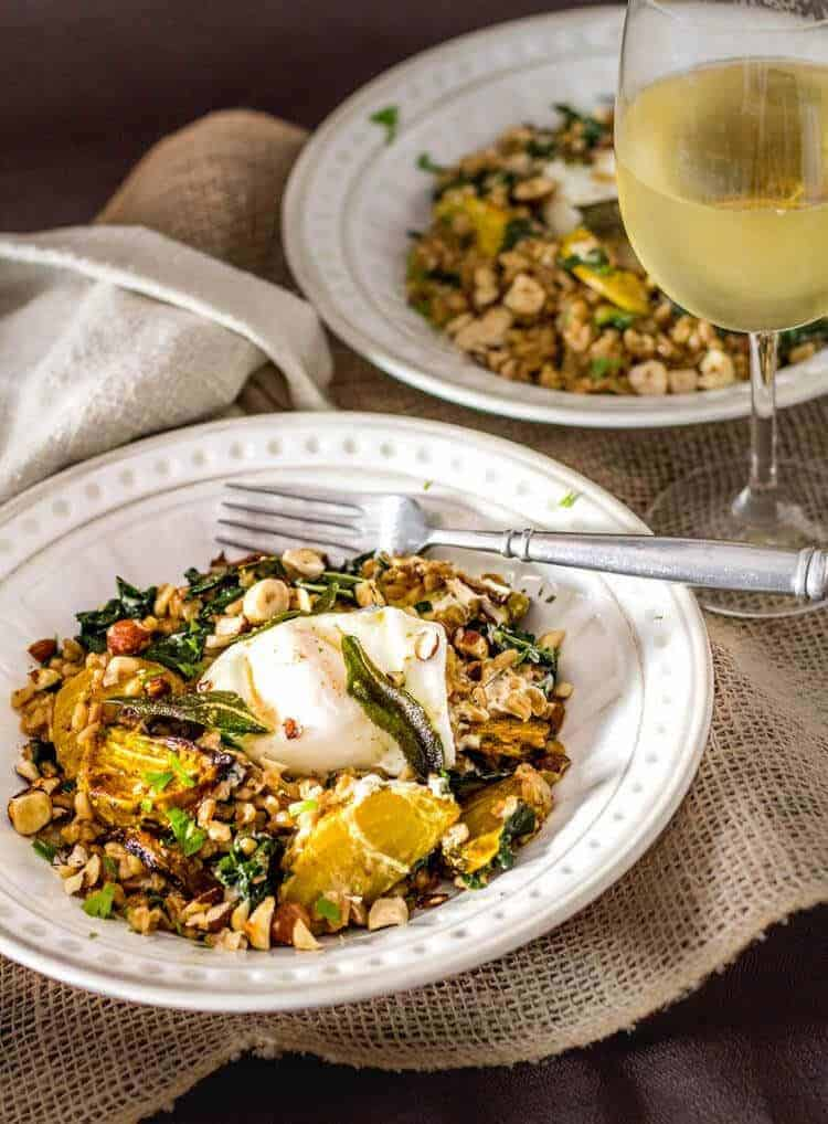 Kale and Roasted Beet Farro with Sage and Hazelnuts - 2 bowls and a glass of white wine.
