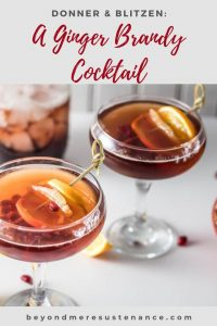 2 coupe glasses with ginger brandy cocktails garnished with orange and pomegranate arils.