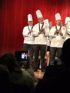3 culinary students, including son Gerritt, on stage at graduation.