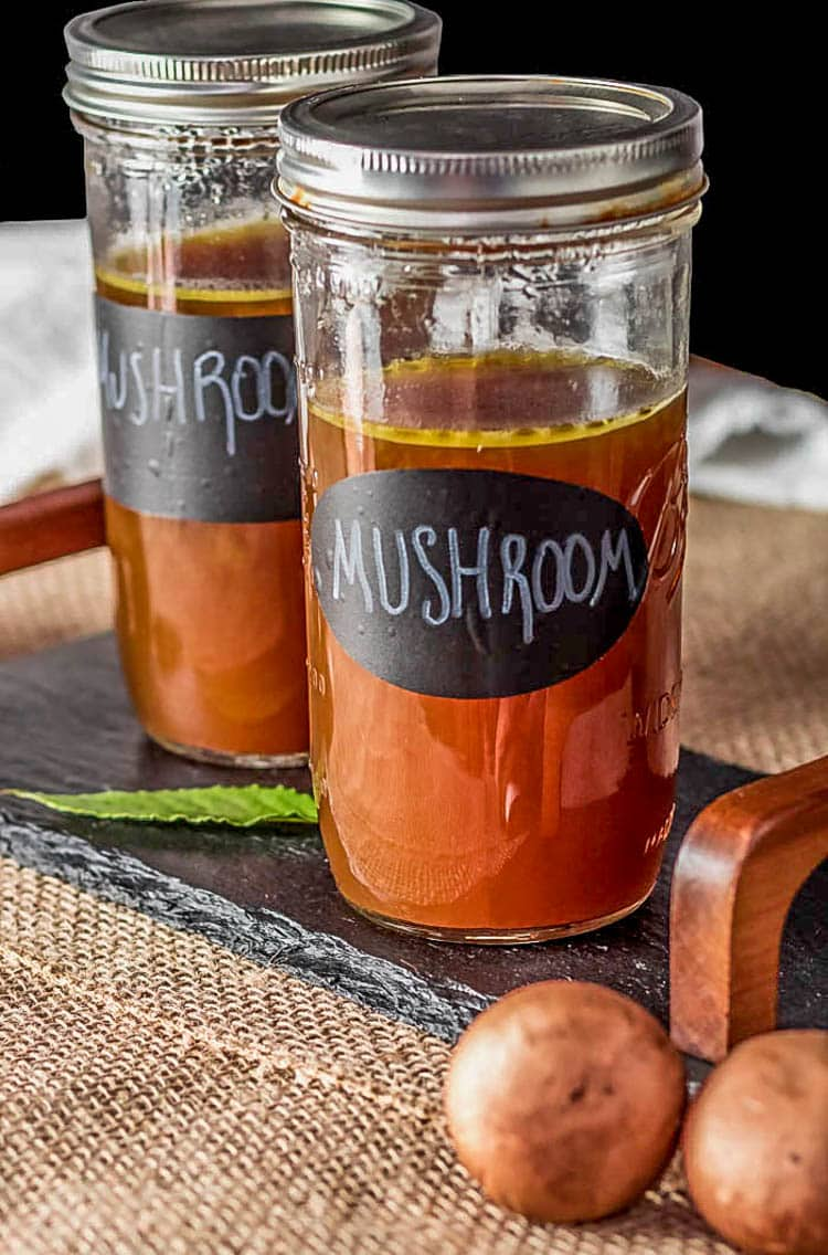 Instant Pot Roasted Mushroom Broth in mason jars on a slate tray.