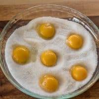 egg yolks in a pie plate filled with salt