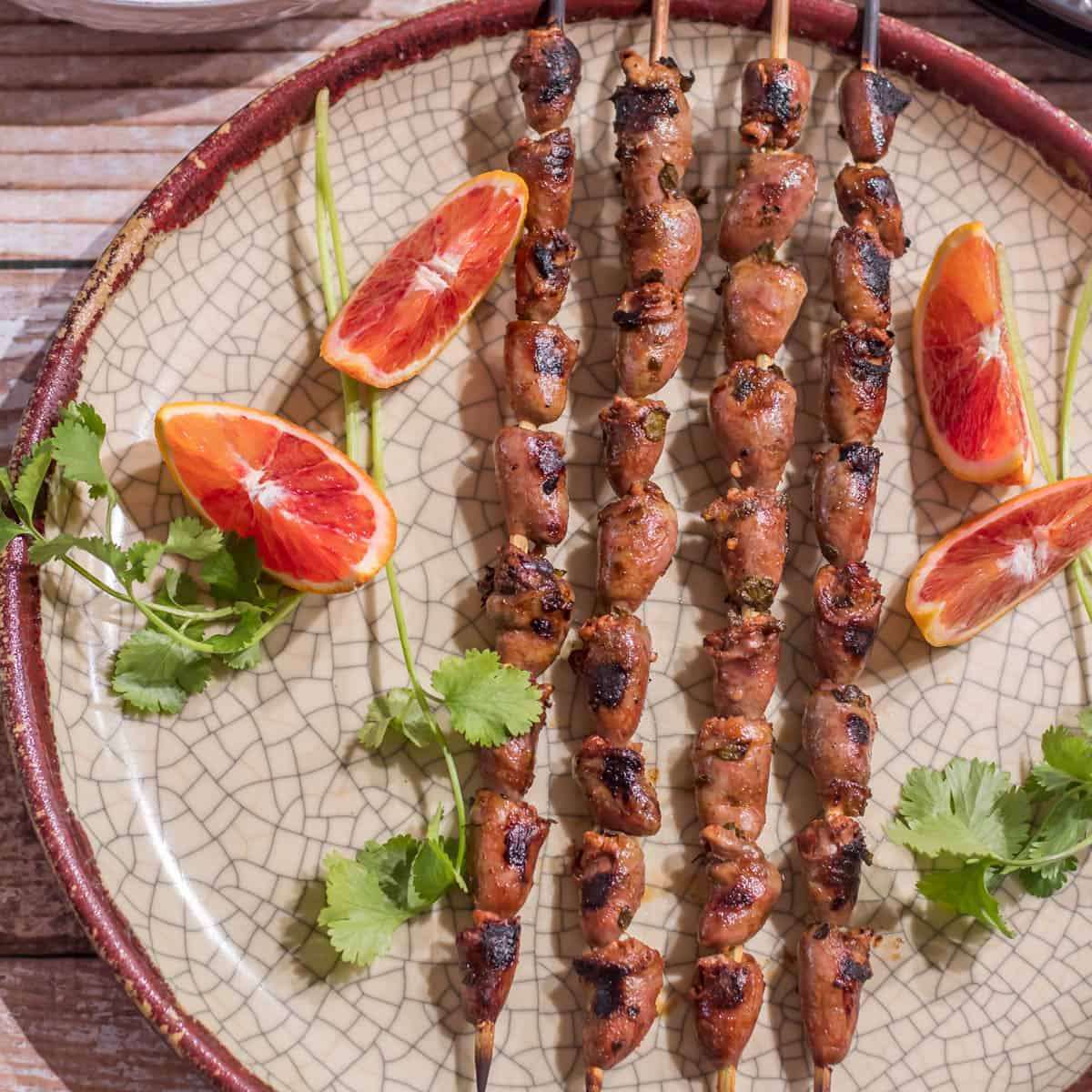 Mexican Grilled Chicken Hearts skewers on a bronze ceramic plate with Mexican Cilantro Rice and blood orange wedges.