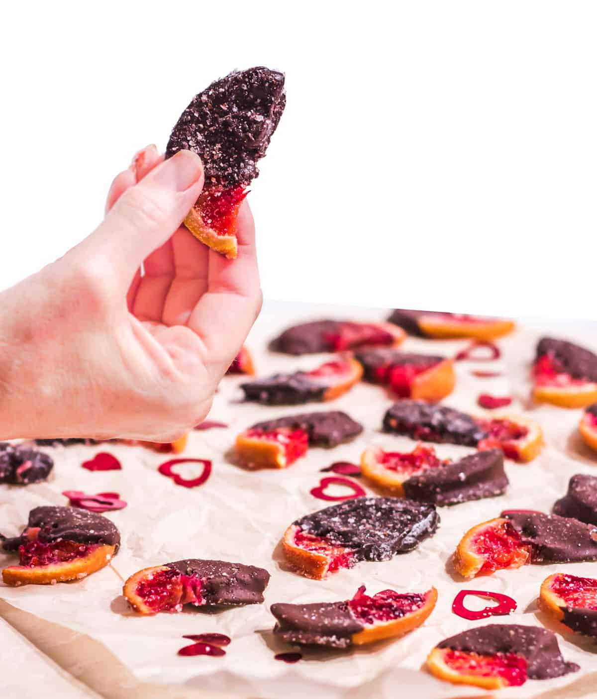 Chocolate Dipped Candied Blood Oranges spread on parchment with one section in hand.