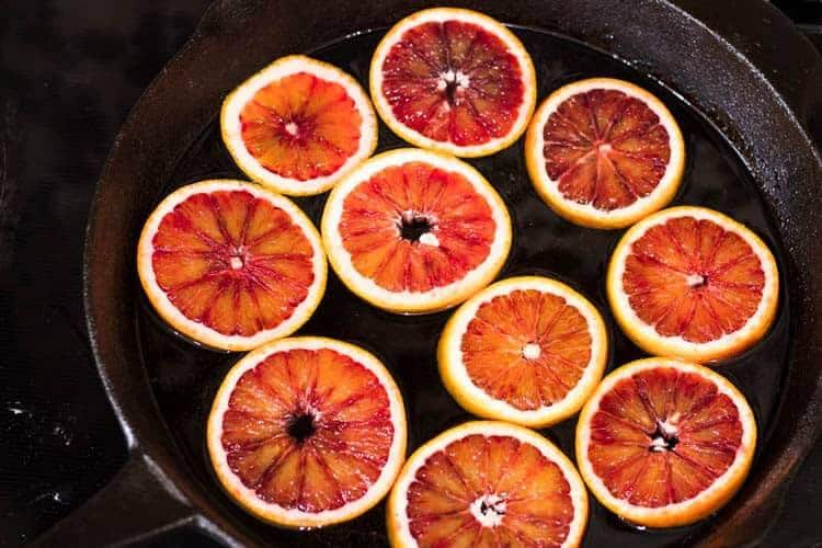 Blood orange slices simmering in sugar syrup in a cast iron skillet.