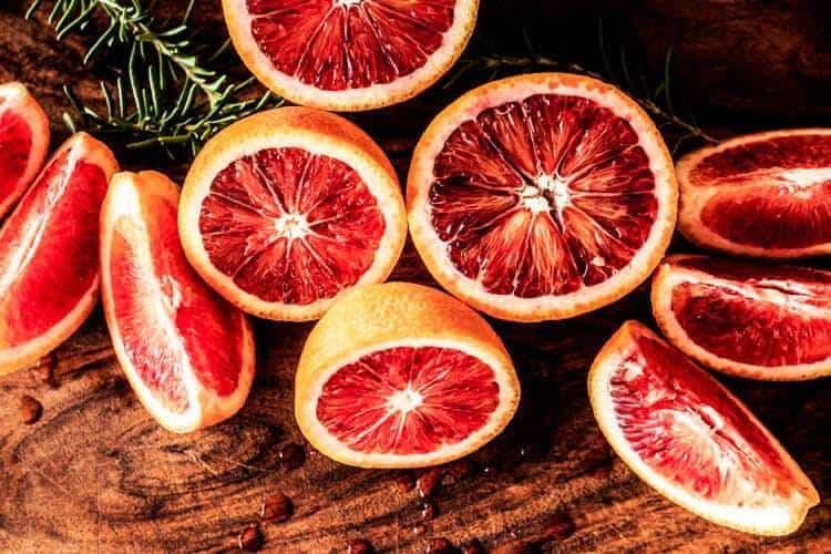 Blood oranges cut in half and wedges with fresh rosemary.