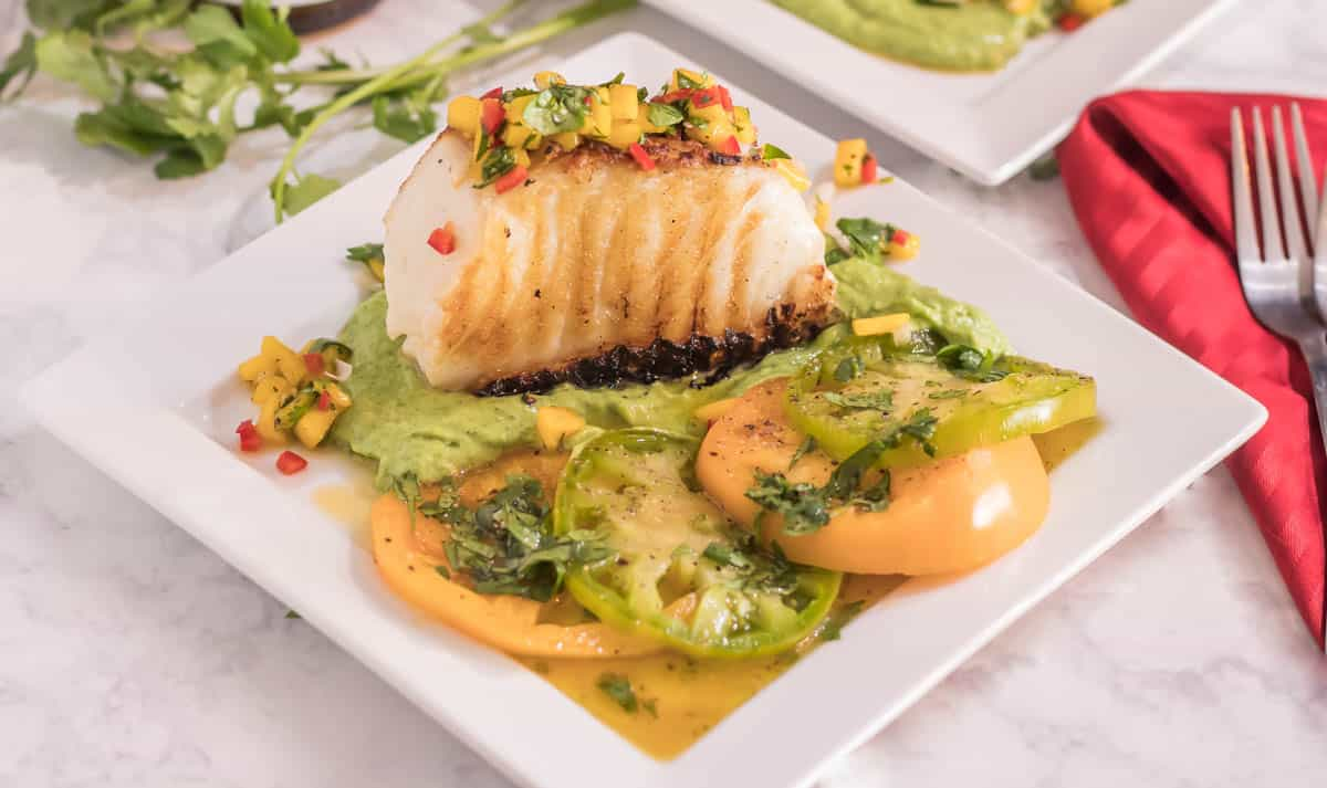 A white square plate with a portion of sea bass atop avocado crema, and topped with mango salsa.