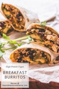 High Protein Vegan Breakfast Burritos on a wood cutting board atop parchment paper.
