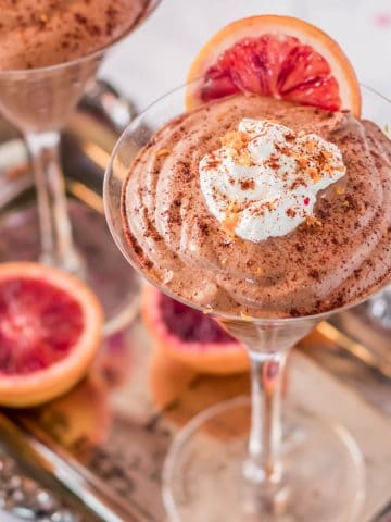The feature image of Mexican chocolate mousse on a silver tray with whipped cream and orange.