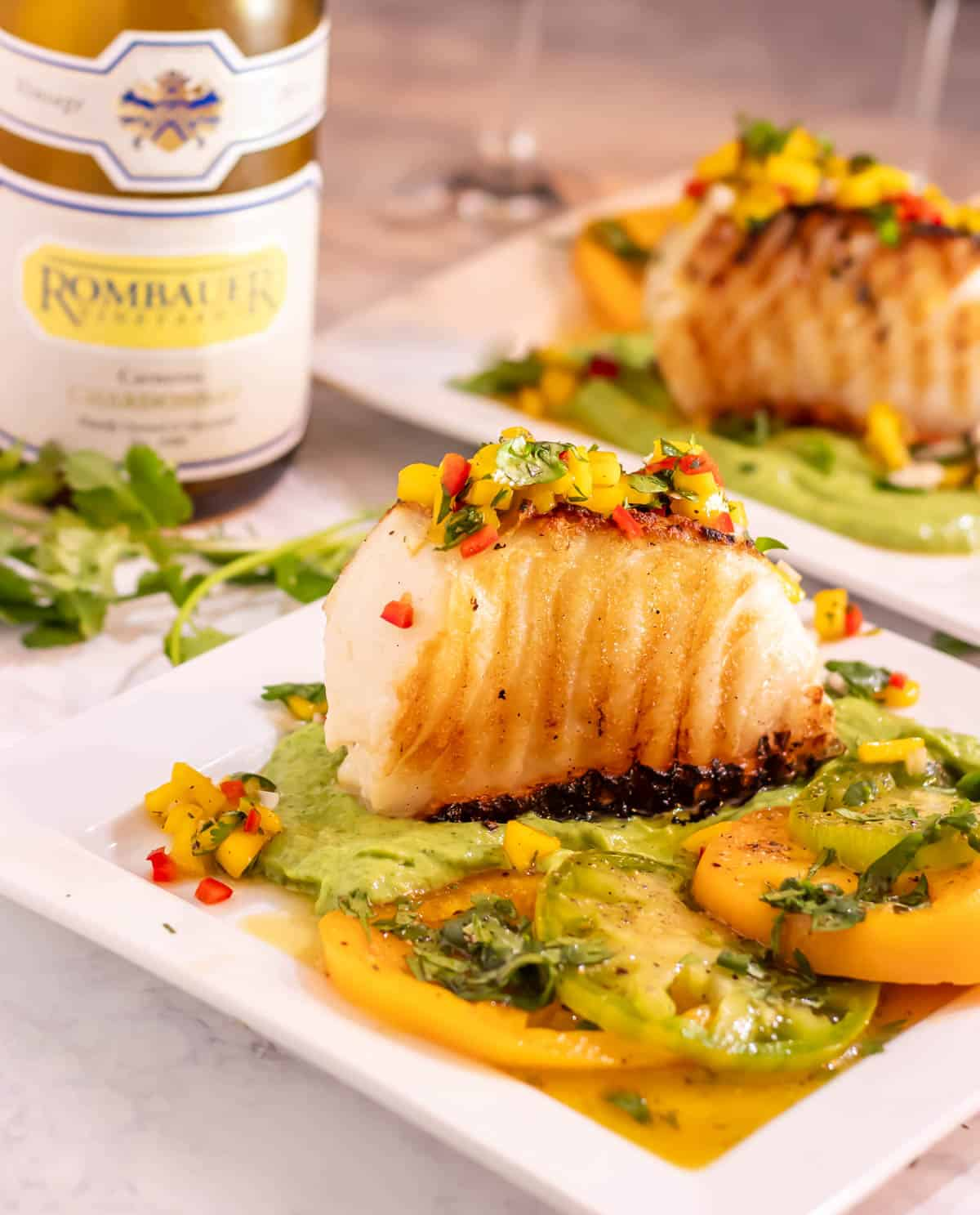 Mexican Grilled Sea Bass on a bed of avocado crema, topped with mango salsa, and garnished with fresh cilantro is healthy, super quick, easy, and so delicious!