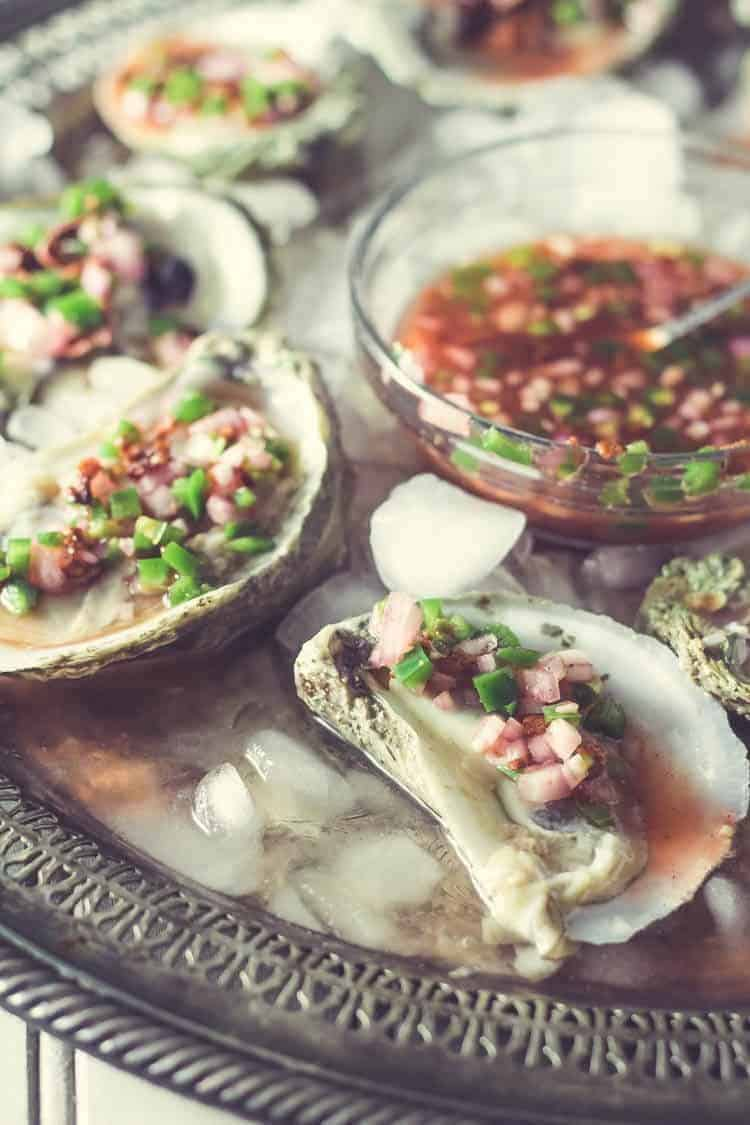 Oysters on the Half Shell with a bowl Blood Orange Mignonette on an antique platter with ice.