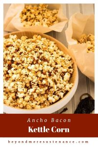 A wood bowl of ancho bacon kettle corn with 2 parchment bags full of popcorn.