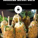 grilled Mexican street corn (elote) on bamboo skewers garnished with cilantro.