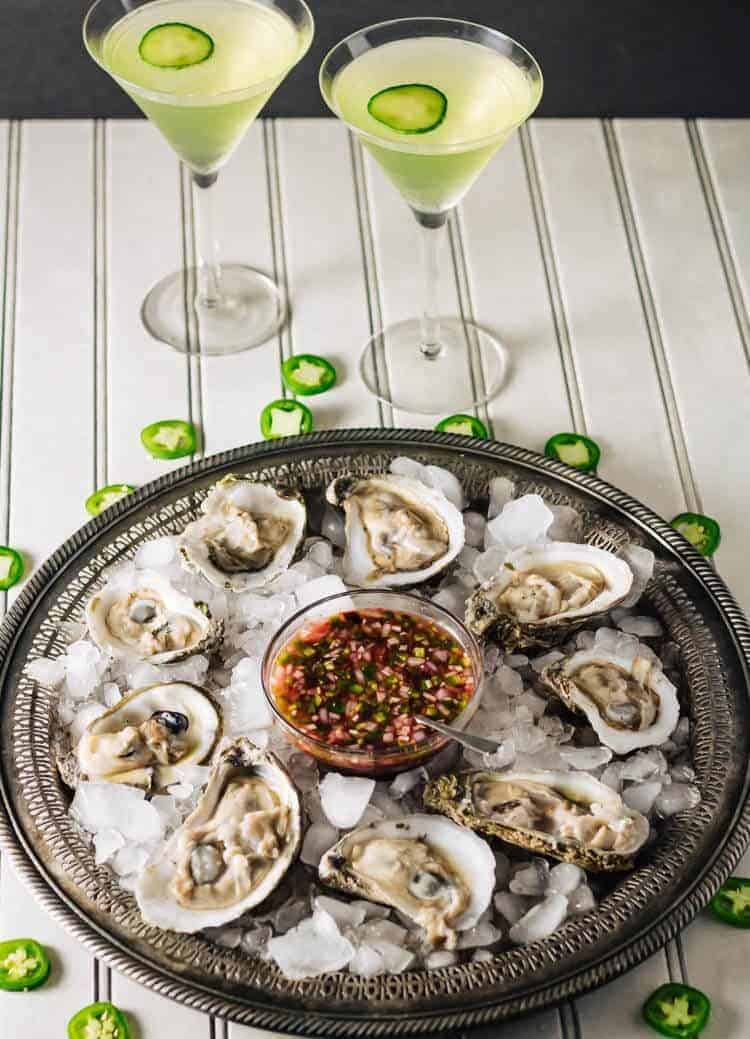 Lemon Cucumber Martini with Basil beside a platter of fresh raw oysters on a silver tray and a bowl of jalapeno mignonette.