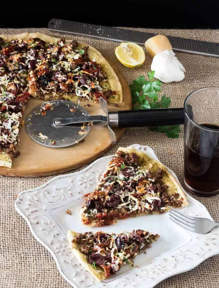Greek Lamb Pizza on a pizza stone with one slice of pizza on a square plate with a dark beer.