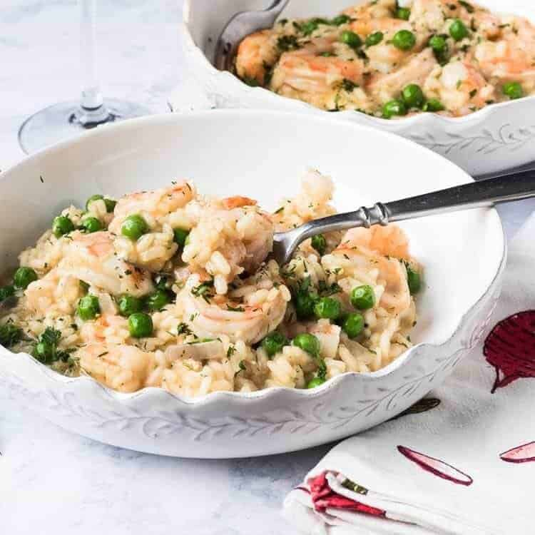 A bowl of spring risotto with a silver fork alongside a spring print napkin.
