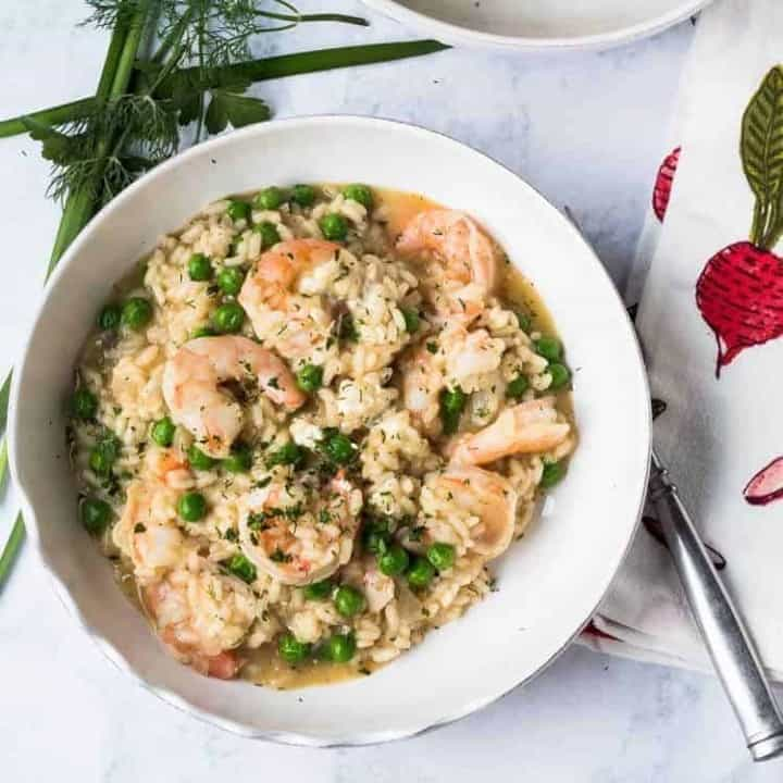 Spring Risotto with Shrimp, Chevre, and English Peas in a white ceramic bowl with fresh herbs.